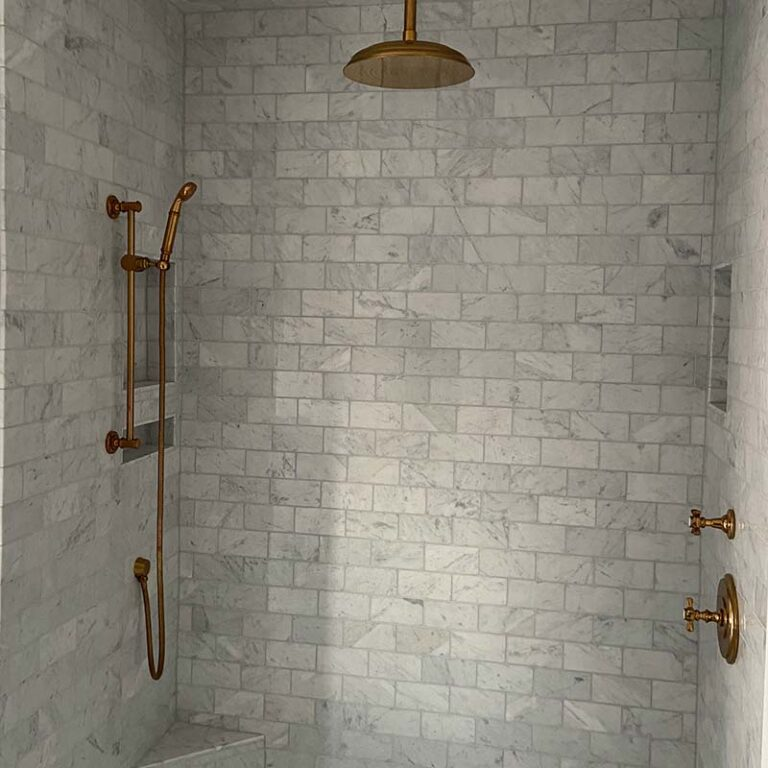 walk-in shower remodel with grey tile and copper finishes